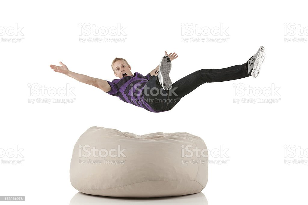 Young man falling on a bean bag stock photo