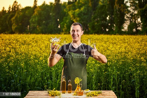 istock A young man farmer or agronomist examines the quality of rapeseed oil on a rape field. Agribusiness concept 1161186503