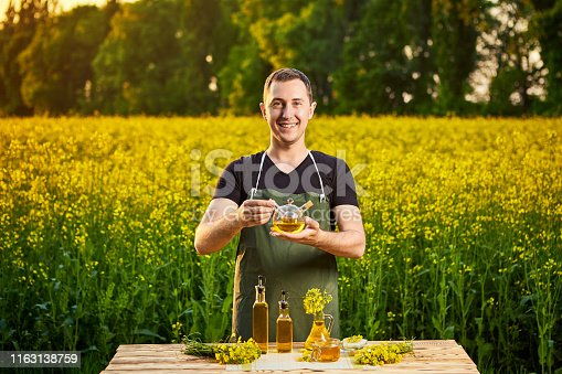 istock A young man farmer or agronomist examines the quality of rapeseed oil on a rape field. Agribusiness concept 1163138759