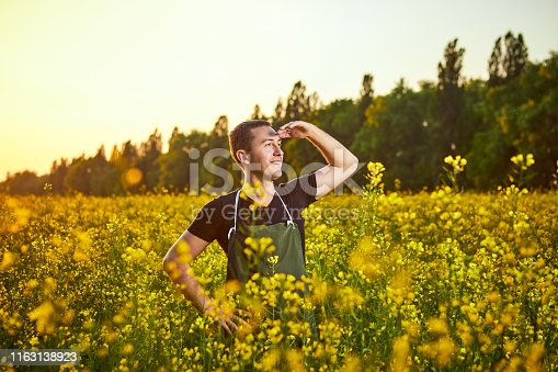 istock A young man farmer or agronomist examines the quality of rapeseed oil on a rape field. Agribusiness concept 1163138923
