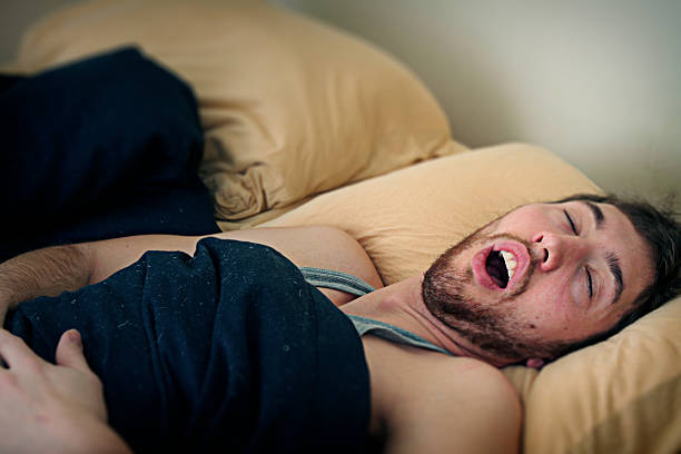 Young Man Fast Asleep in Bed A young adult sleeping / snoring soundly in his bedroom with an open mouth.  Horizontal with copy space. mouth open stock pictures, royalty-free photos & images