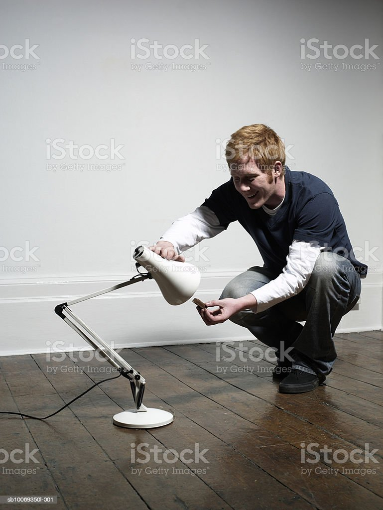 Young man feeding lamp, indoors royalty-free stock photo