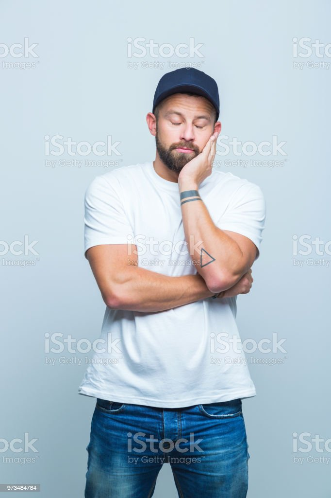 Young man feeling alone Portrait of young man standing on white background looking sad. Adult Stock Photo
