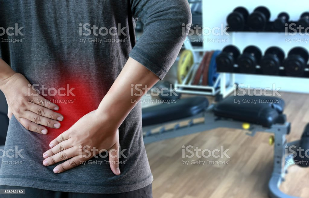 young man Feeling suffering  Lower back pain  Pain relief concept stock photo