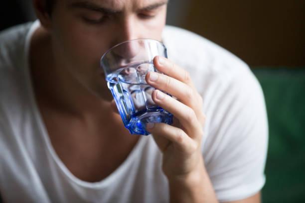年輕人感覺口渴脫水持有玻璃飲用水, 特寫 - 口渴 個照片及圖片檔