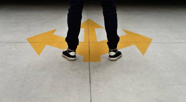 Junge Füße und drei gelbe Pfeile auf dem Boden gemalt – Foto