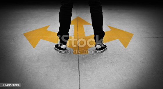 Young man feet and three yellow arrows painted on floor.