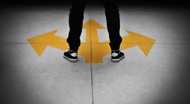 young man feet and three yellow arrows painted on floor - definite stock pictures, royalty-free photos & images
