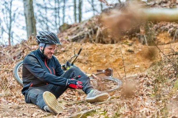 Young man fell off mountain bike stock photo