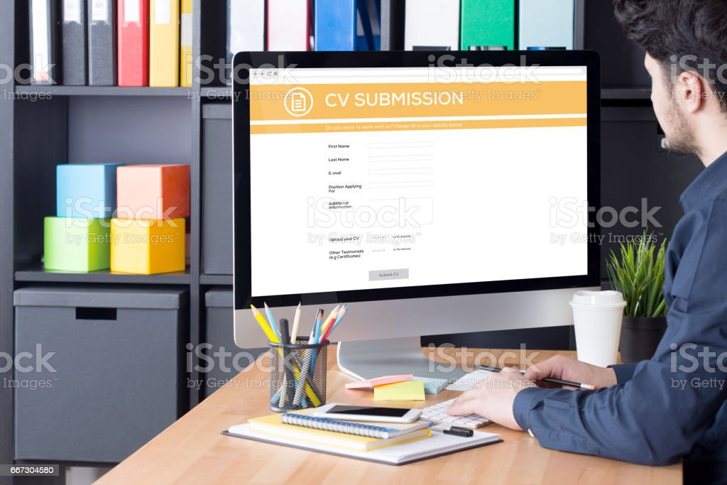 Young man filling Job application form on internet stock photo