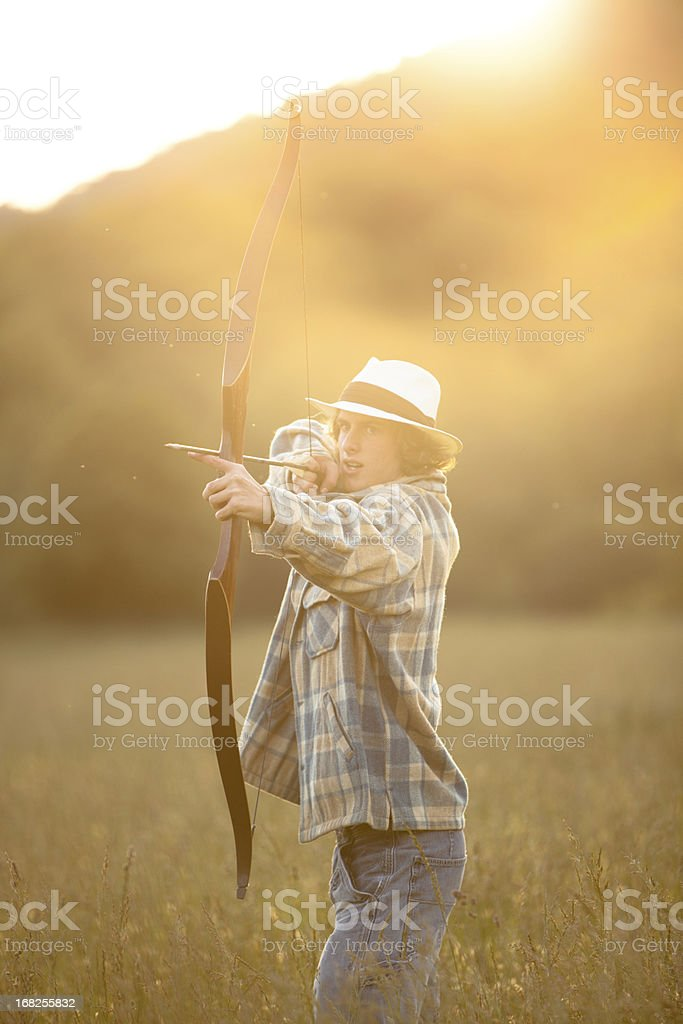 Young man firing bow and arrow royalty-free stock photo