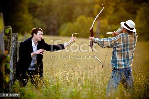 istock Young man firing bow and arrow towards a businessman 125143322