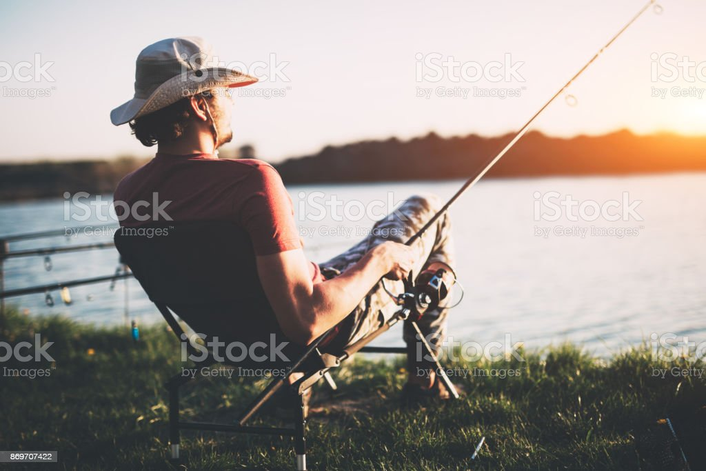 Young man fishing at pond and enjoying hobby stock photo