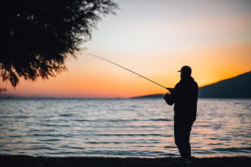 Young Man Fishing at the Beach at Sunset