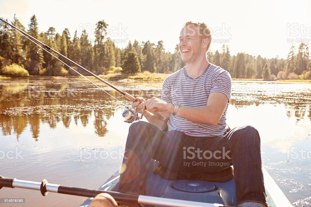 Young Man Fishing From Kayak On Lake stock photo