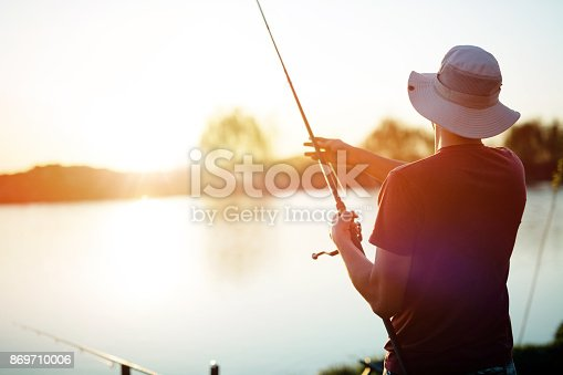 914030378 istock photo Young man fishing on a lake at sunset and enjoying hobby 869710006