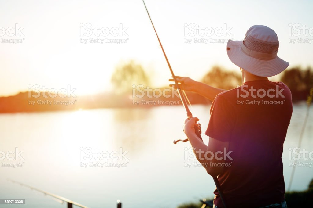 Young man fishing on a lake at sunset and enjoying hobby stock photo