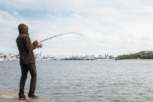 若い男川の回転と釣り - 釣り ストックフォトと画像