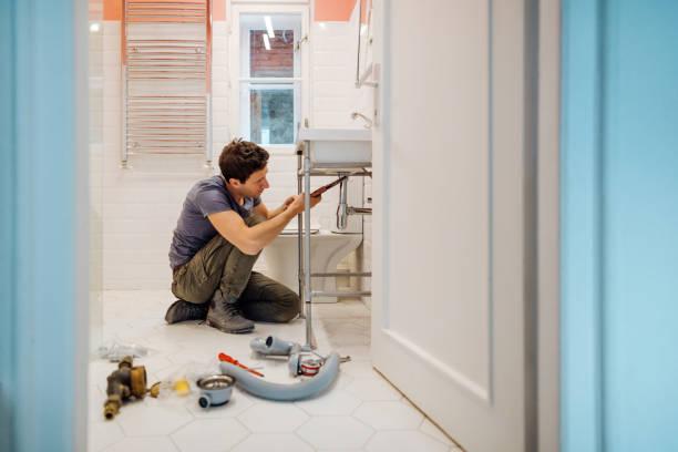 młody mężczyzna naprawiający wyciek pod umywalką w łazience - naprawiać zdjęcia i obrazy z banku zdjęć