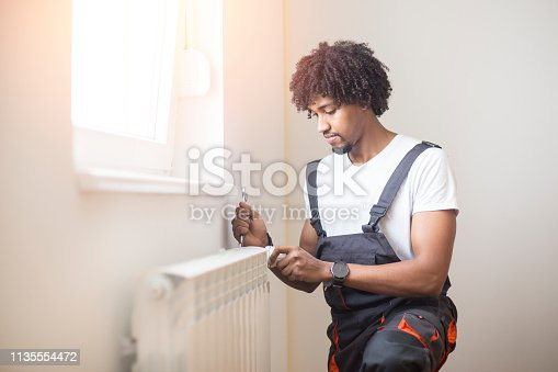 Young man fixing a radiator in an apartment. About 25 years old, African male.