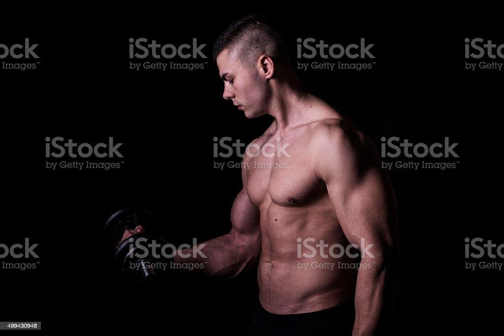 young man flexes his bicep stock photo