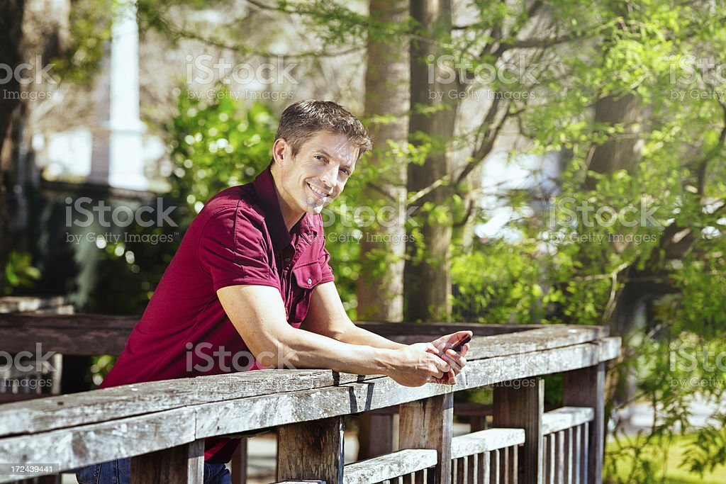 Young man Flirting in Park holding mobile phone Horizontal stock photo