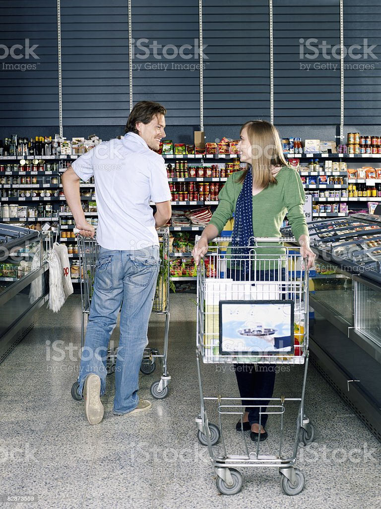 young man flirting with young woman in supermarket foto stock royalty-free