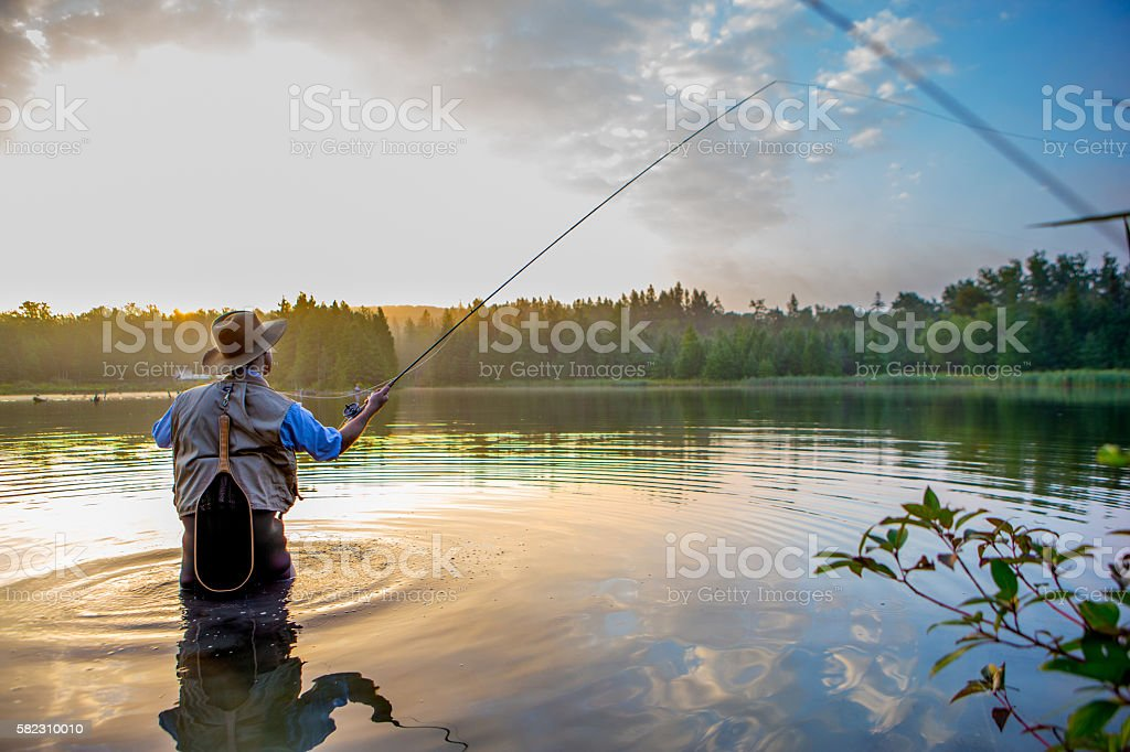 Young man flyfishing at sunrise stock photo