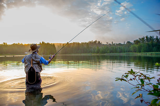young man flyfishing at sunrise - fishing stock pictures, royalty-free photos & images