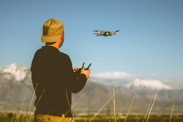junger mann fliegen eine drohne in der abenddämmerung mit bergen im hintergrund - flugdrohne stock-fotos und bilder