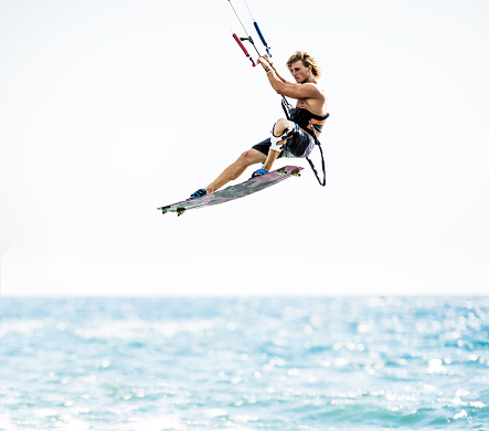 Young man flying with kiteboard above the sea.