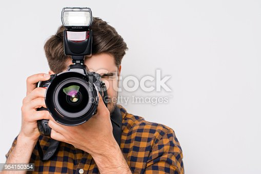 Young man focusing with digital camera  isolated on white background