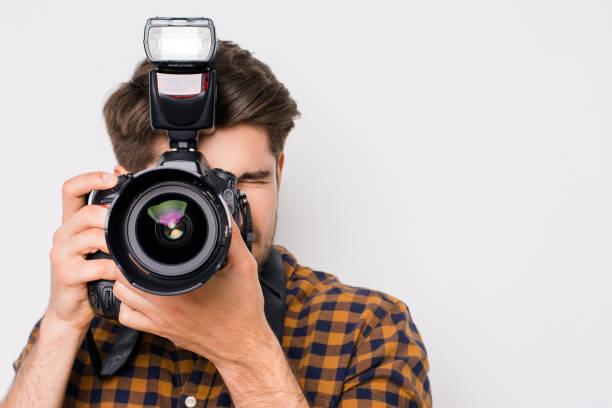 Jeune homme mise au point avec appareil photo numérique isolé sur fond blanc - Photo