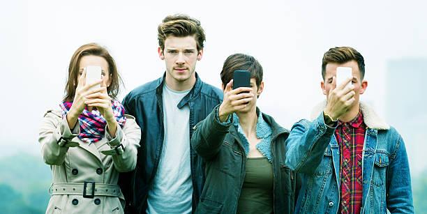 jovem frowns como amigos estão obcecados com telefones - standing out from the crowd (expressão inglesa) - fotografias e filmes do acervo