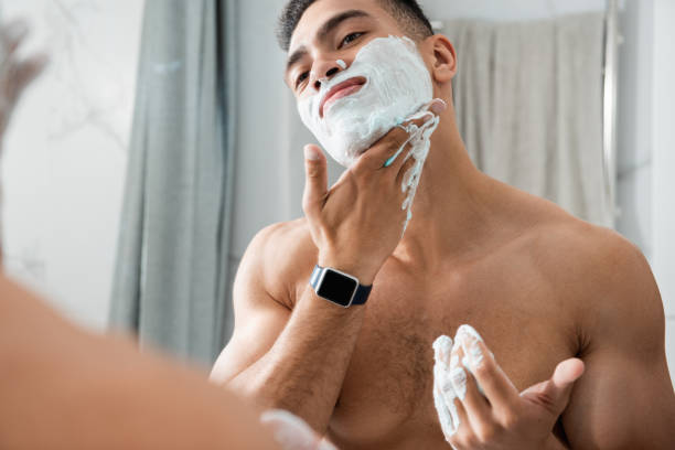 young man gently spreading shaving foam on face - shaving cream stock pictures, royalty-free photos & images