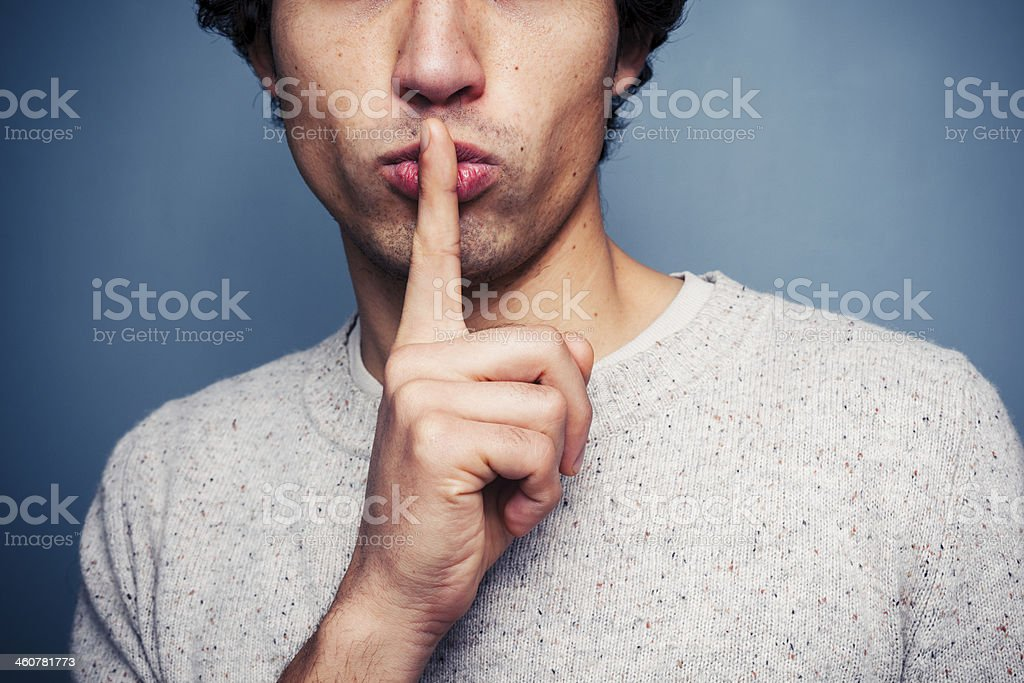 Young man gesturing hush with finger on lips stock photo