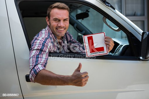 1051147634 istock photo Young man gesturing thumbs up holding a learner driver sign 664888862