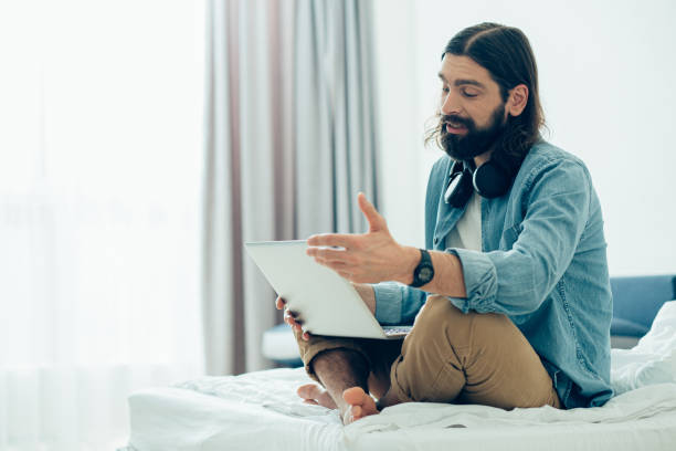 Young man gesturing while having online meeting at quarantine stock photo