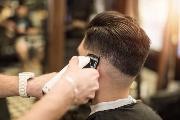 Young man getting a modern haircut. stock photo