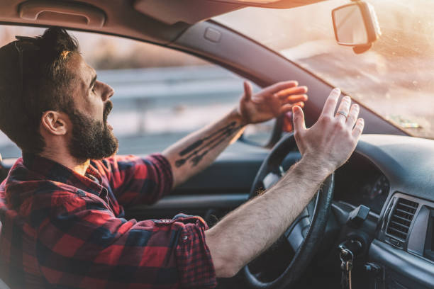 Young man getting angry on the road Side view image of irritated young man shouting at other drivers while driving on the highway anger stock pictures, royalty-free photos & images