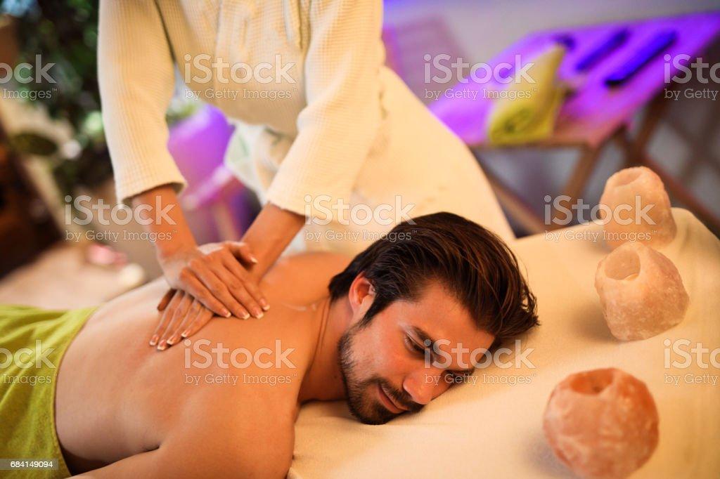 Ung man får tillbaka massage på health spa royaltyfri bildbanksbilder