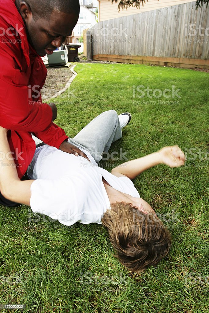 Young Man Getting Beaten on the Ground royalty-free stock photo