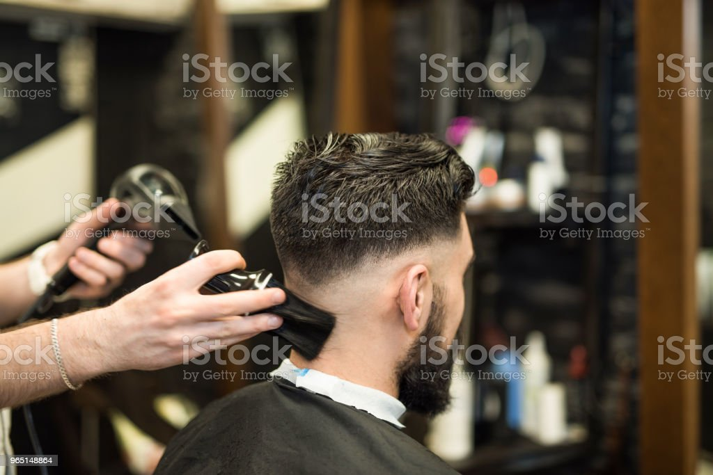 Young man getting cleaned up after getting a haircut. zbiór zdjęć royalty-free