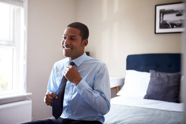 Young Man Getting Dressed In Bedroom For First Day At Work In Office stock photo