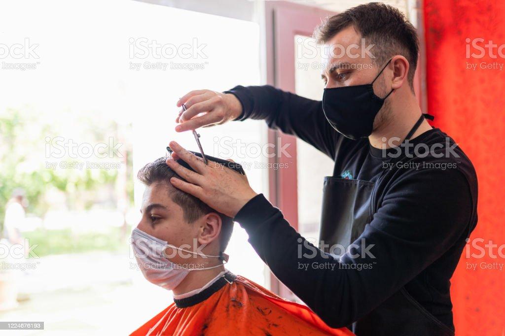 jeune homme obtenant la coupe de cheveux au salon de coiffure - Photo de 14-15 ans libre de droits