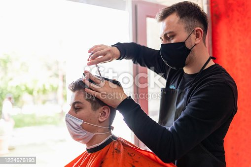young man getting haircut at the barbershop