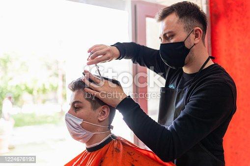 young man getting haircut at the barbershop
