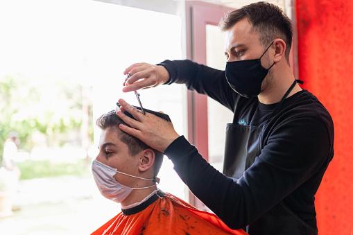 Photo libre de droit de Jeune Homme Obtenant La Coupe De Cheveux Au Salon De Coiffure banque d'images et plus d'images libres de droit de 14-15 ans