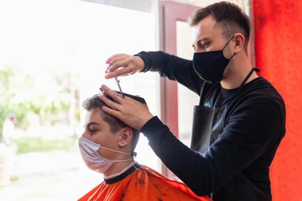 jeune homme obtenant la coupe de cheveux au salon de coiffure - couper les cheveux photos et images de collection