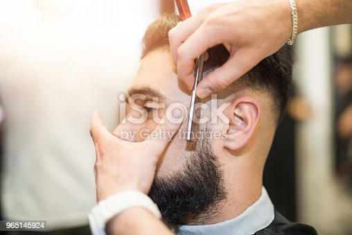 622527180istockphoto Young man getting his beard cut. 965145924